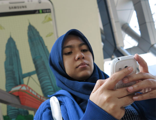 Malaysian Girl with cellphone (610x470)