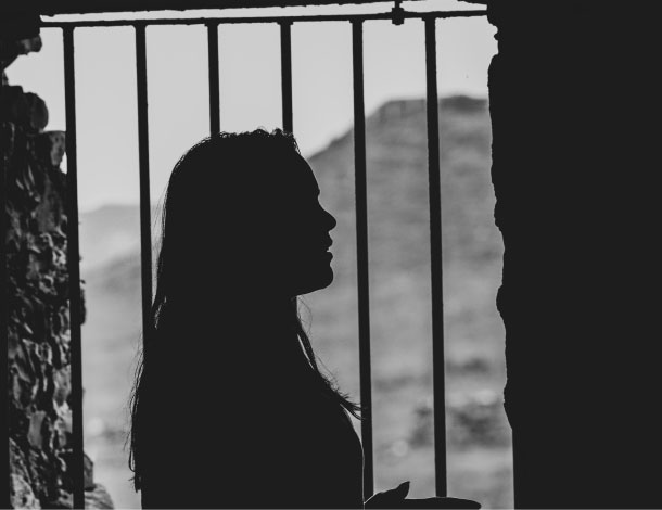 Deprivation of liberty / woman behind bars (Photo : Denis Oliveira | Unsplash)  610x470