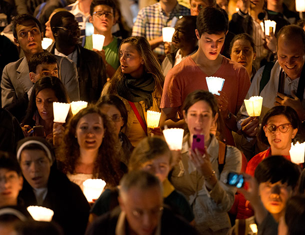 OURs report: Group of people singing with candles in hand - AV Dezign (610x470)